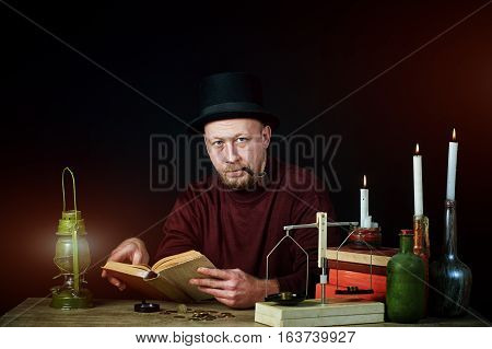 Stylized portrait of a man in a top hat with a pipe , old books and candles