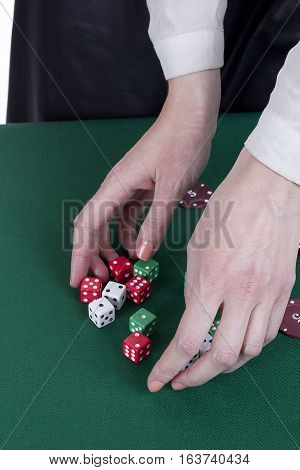 Her hands croupier with dice and chips in casino