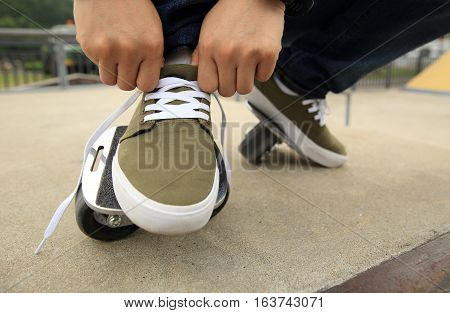 freeline skateboarder tying shoelace at skatepark ramp