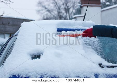 Hand of woman using brush and remove snow and ice from car and windscreen concept of transportation and winter