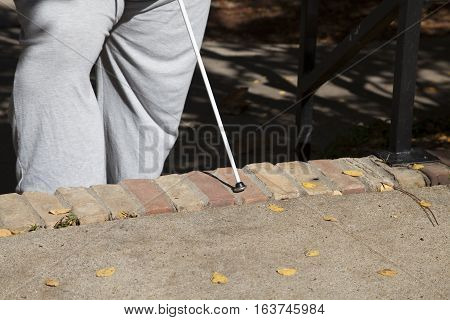 Blind person using a walking cane to navigate steps