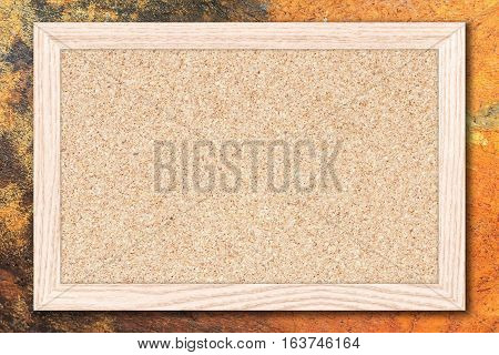 Cork board or Empty bulletin board with a wooden frame on cement wall background with copy space for text or image.