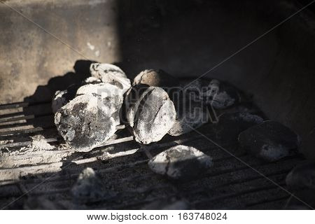 Ashy charcoal sitting in a barbecue pit