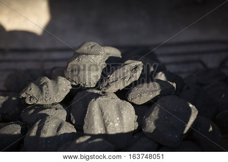 Unlit charcoal waiting in a barbecue pit