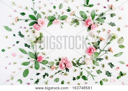 Round frame made of pink and beige roses green leaves branches floral pattern on white background. Flat lay top view. Valentine's background