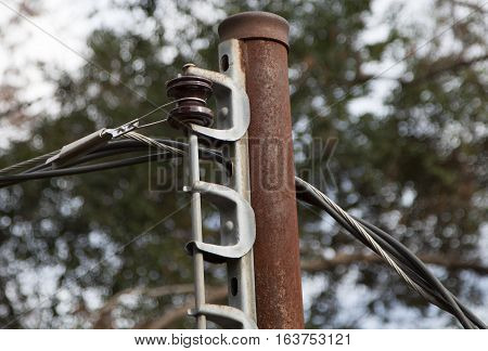 Rusted old electric pole and lines running from it