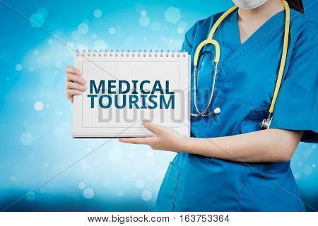 Doctor Shows Medical Tourism Text On White Line Paper Book.