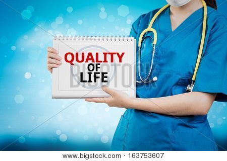 Doctor Shows Quality Of Life Text On White Line Paper Book.