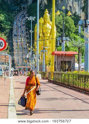 KUALA LUMPUR. MALAYSIA - JANUARY 13. 2014: Pilgrims at an entrance to the Batu Caves and Golden statue of hindu god Lord Murugan
