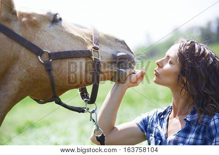Woman and horse together outdoors at paddock