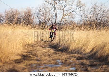 KHABAROVSK RUSSIA - OCTOBER 23 2016: Enduro bike rider on a field with dry grass in autumn