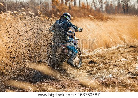 KHABAROVSK RUSSIA - OCTOBER 23 2016: Enduro bike rider on a field with dry grass in autumn. The motorcycle skids and makes a lot of mud splashes. Focus on mud
