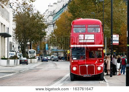 London UK - November 19 2016 - People boarding the red bus for an afternoon tea bus tour
