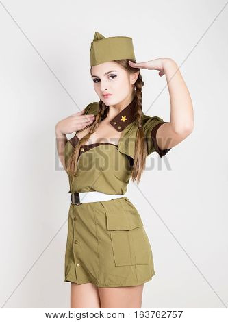sexy fashionable woman in military uniform and forage-cap, put a hand to her head and salutes.