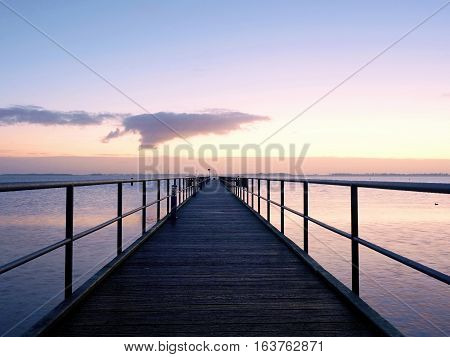 Long Wooden Pier On The Baltic Coast During Autumn Morning. Cold Weather