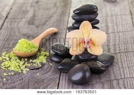 Phalaenopsis orchid, bath salt and black stones on wooden background