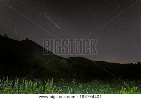 Shooting star in the night sky above the ridge of the hills. Starry landscape with meteor. Star trail.