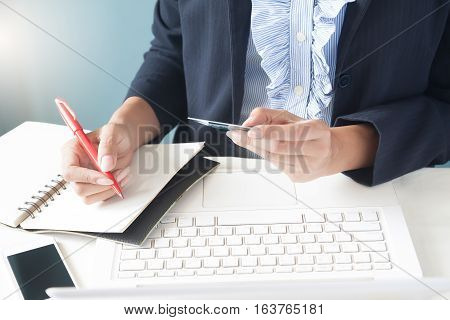 Business woman in dark suit holding credit card using laptop and writting on notebook Business and online shopping concept