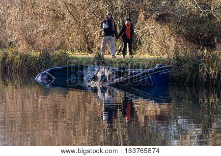 Bath UK - January 2 2017: Partially submerged canal boat after fire with onlookers. Damaged hull of narrow boat in Kennet and Avon Canal after being gutted by fire with pedestrians