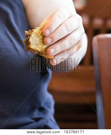 Woman holding beef taco that has been mostly eaten