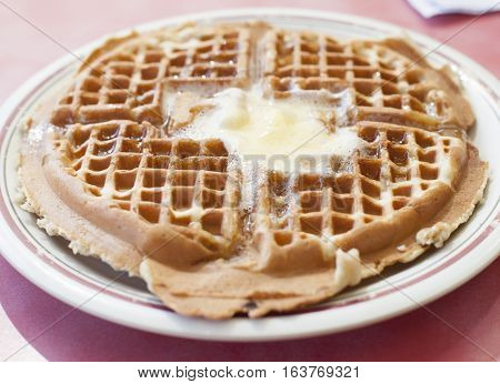 Melted butter on top of an uncut waffle