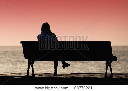 Silhouette of young woman sitting alone on the bench in front of the sea