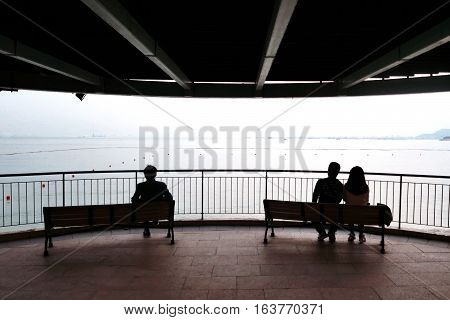 The silhouette of couple man and the wooden bench