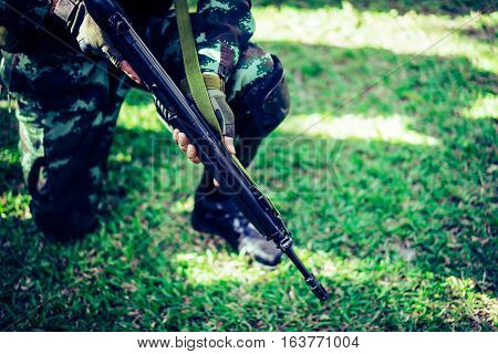 Military observer seats on the grass with M16.