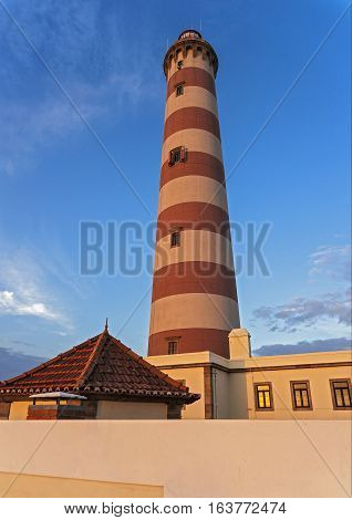 Costa Nova do Prado ( Portugal). Brick lighthouse on the Atlantic coast . A lovely spring day is nearing evening lighthouse painted by the setting sun . Blue sky with a few clouds.