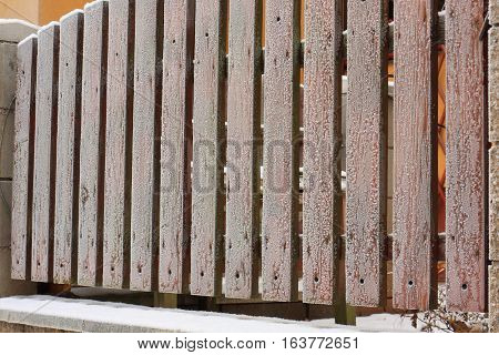 Frozen and snowy fence of wooden planks