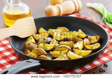 Fresh fried potato wedges with rosemary and spring onion on table