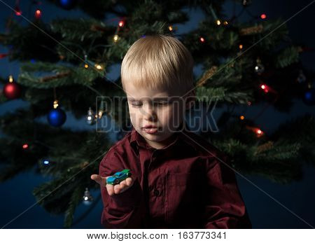 Kid and multicolor spruce with decorations and lights bokeh. Little boy and toy car under the multicoloured Christmas tree