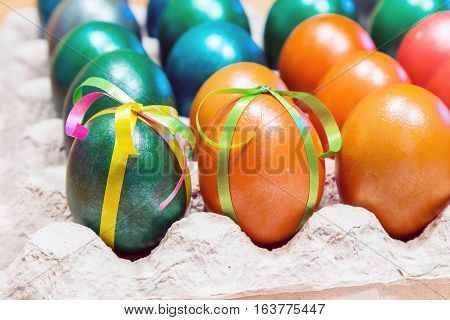 Brightly colored bow decorated easter eggs in egg carton holder, holiday background