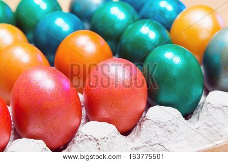Brightly colored Easter eggs in egg carton holder, holiday background