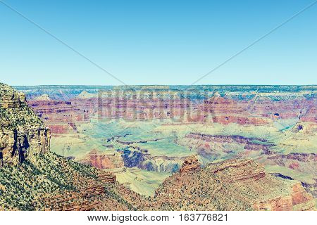 View of the Grand Canyon from the top on a sunny clear day. Diverse colors of geological formation of Canyon.