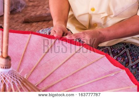Worker cover and glue with perssimon ferment on Handmade umbrella of the village Bo Sang Chiang mai Thailand.