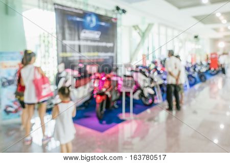 Abstract people walking in motor show car show room blurred defocusing background. Concept of business social gathering for meeting exchange.