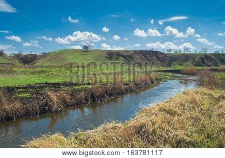 Ukrainian rural landscape with smal river Sura at early spring season.