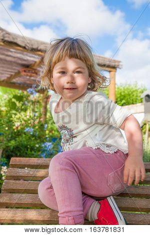 portrait of two years old blonde child playing active on wooden lounge deck chair at garden