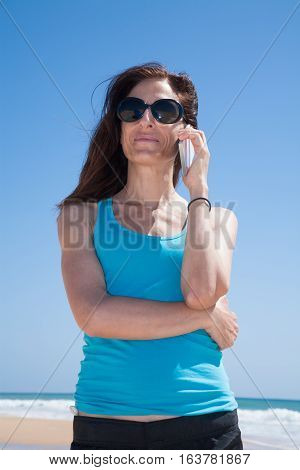 Blue Shirt Woman Talking On Mobile Phone At Beach