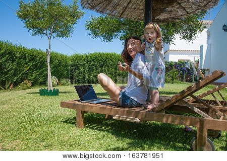 Funny Little Child And Mother With Laptop At Garden