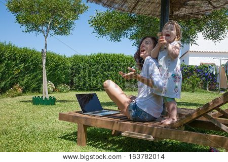 Funny Woman With Laptop And Little Child At Garden