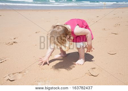Little Girl Crouch And Writing With Finger On Sand Beach