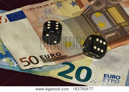 On a red cloth of the visible bills twenty and fifty euros. On the bills are black cubes for poker