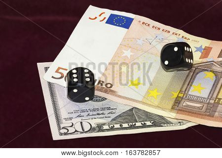 On a red cloth of visible part of the fifty dollar bills and fifty euros. On the bills are black cubes for poker