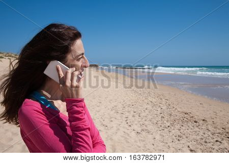 Side Of Pink Shirt Woman Talking On Mobile At Beach