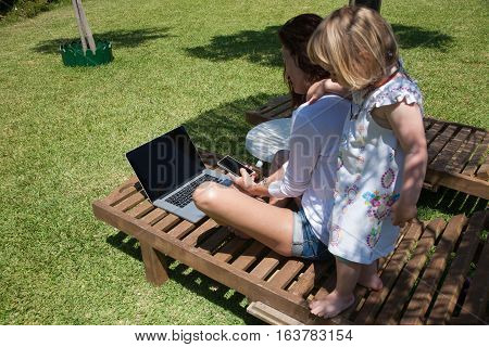 Woman Laptop Smartphone And Little Child On Lounge Chair