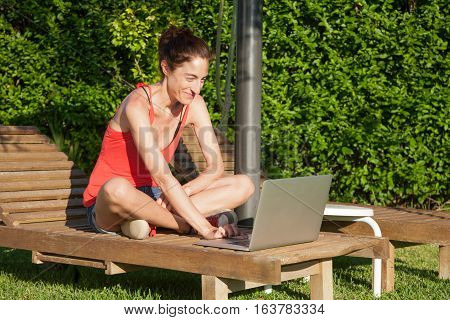 Woman Using Laptop On Lounge Deck Chai