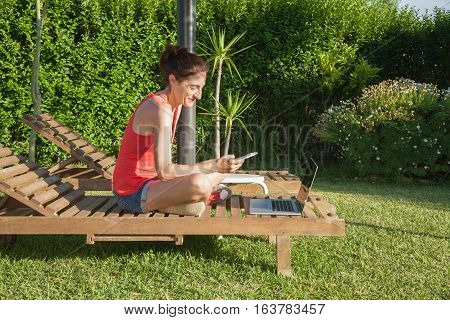 Woman With Phone And Computer On Lounge Wooden Deckchair