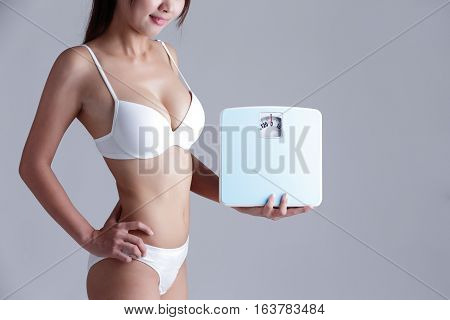 Health and slim body of woman holding scale isolated on gray background asian beauty